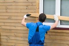 De mens in overtrekken sluit vensters met raad om het huis te beschermen royalty-vrije stock foto