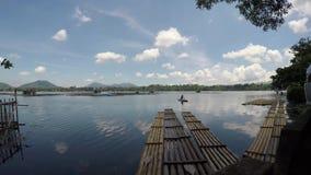 De mens paddelt bamboevlot naast bamboepolen worden gebruikt om Vissenkooien te handhaven die stock video