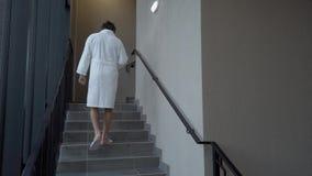 De mens in pantoffels beklimt de treden stock video