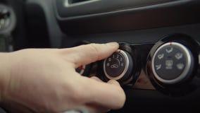 De mens past het verwarmen en ventilatiesysteem binnen auto aan, close-up van hand stock footage