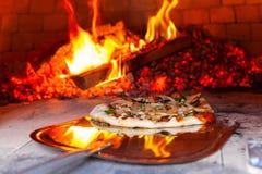 De mens plaatst een vers voorbereide pizza in een openluchtbroodoven - stock afbeelding