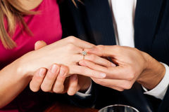 De mens plakt ring op vinger van fiancé stock foto's