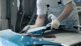 De mens poetst detail van blauwe auto op stock footage