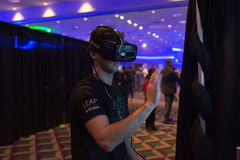 De mens probeert de virtuele Oculus-hoofdtelefoon van de Spleetwerkelijkheid Stock Afbeelding