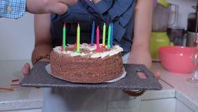 De mens probeert lichten de kaarsen op verjaardagscake stock footage