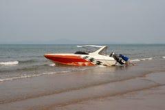 De mens probeert om de boot at low tide te duwen Stock Afbeeldingen