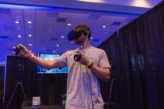 De mens probeert virtuele van de werkelijkheidshoofdtelefoon en hand controles Stock Afbeelding