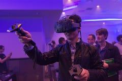 De mens probeert virtuele van de werkelijkheidshtc Vive hoofdtelefoon en hand controles Stock Foto's