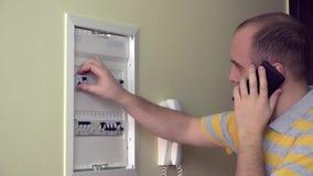 De mens raadpleegt telefonisch over elektrofout in eigen ruimte 4K stock footage