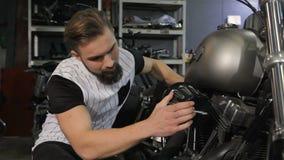 De mens raakt de compressor van de bijl op de motorfietsworkshop stock video