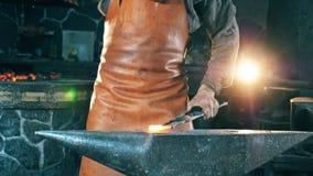 De mens raakt een heet mes met een hamer terwijl het werken bij smeedt stock videobeelden