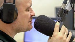 De mens radiodj spreekt in microfoonclose-up stock videobeelden