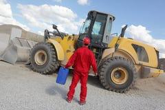 De mens in rode eenvormig met benzine kan, bulldozer op achtergrond, achtermening Stock Foto's