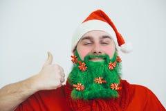 De mens in rode kleren met groene baard toont de duim omhoog ondertekent royalty-vrije stock fotografie