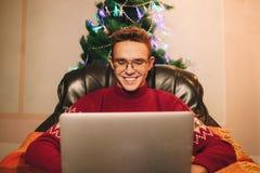 De mens in rode sweater maakt een aankoop op Internet via laptop stock fotografie