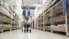 De mens rolt karretje met voedsel beetwen planken en kiest producten in supermarkt, steadicam schot stock videobeelden