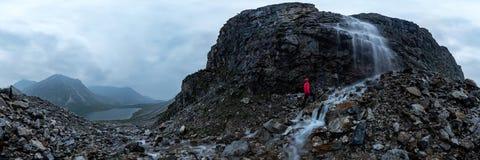 De mens in rood bevindt zich onder een waterval op een zwarte rots in de bergen op een bewolkte regenachtige dag cilindrisch pano stock foto's