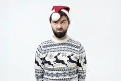 De mens in rood frowns van de Kerstmishoed gezicht met ongenoegen, heeft uitdrukking geïrriteerd, die ontevredenheid zijn royalty-vrije stock afbeelding