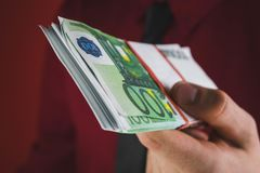 de mens in rood kostuum houdt een pakje van geld in zijn hand op rode achtergrond stand stock afbeeldingen