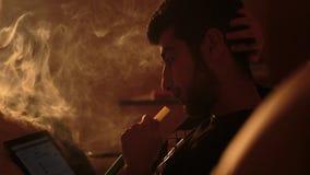 De mens rookt een waterpijp en gebruikt tablet Stock Afbeeldingen