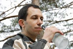 De mens ruikt een fles met alcoholisch Stock Fotografie