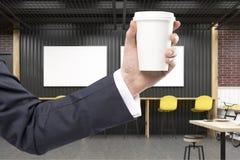 De mens ` s dient een koffiebinnenland met twee horizontale affiches in Stock Foto