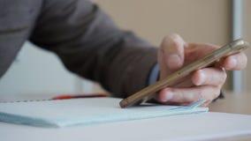 De mens ` s dient kostuum in houdt telefoon in hand en schrijft met pen stock videobeelden