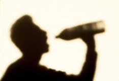 De mens in schaduw, drinkt een water Royalty-vrije Stock Fotografie