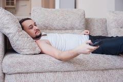De mens schakelt TV liggend op de laag stock fotografie