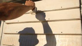 De mens schildert een verfborstel met witte verf een houten muur op de straat stock footage