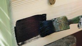 De mens schildert de houten oppervlakte met zwarte verf stock footage