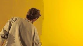 De mens schildert muur in geel stock video