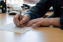 De mens schrijft iets op een Witboek. Het bureauwerk Royalty-vrije Stock Afbeelding