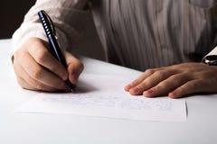 De mens schrijft op een blad van document royalty-vrije stock fotografie