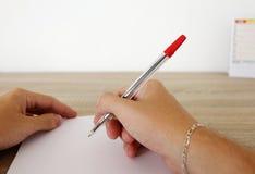 De mens schrijft op het document met pen Stock Afbeelding