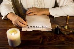 De mens schrijft op perkamentvrijheid royalty-vrije stock afbeelding