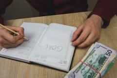 de mens schrijft zijn doelstellingen in zijn notitieboekje, op de lijst is een bundel van contant geld royalty-vrije stock afbeelding