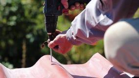 De mens schroeft een schroef in het dak Voorraadlengte De professionele arbeider werkt langs aan installatie van een dak van een  stock footage