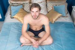 De mens in sexy ondergoed zit op bed in slaapkamer stock foto