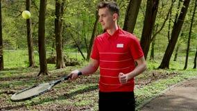 De mens slaat de tennisbal van de racket Jongere speeltennis Een persoon kleedde zich in een rode t-shirt en een zwarte stock footage