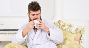 De mens slaperig in badjas, drinkt koffie, genietend van aroma in luxehotel in ochtend, witte achtergrond Elitevrije tijd stock fotografie