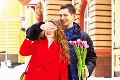 De mens sloot ogen van zijn girfriend om een verrassing te maken Mooi jong paar die samen door stadsstraten lopen stock afbeeldingen