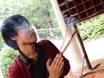 De mens sluit zijn ogen en bidt voor Boedha met joss stok Royalty-vrije Stock Foto's
