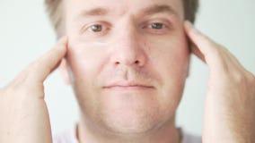 De mens smeert vochtinbrengende crème op gezicht stock video