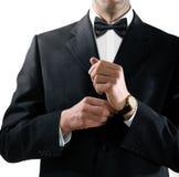 De mens in smoking zet op horloge Royalty-vrije Stock Foto's