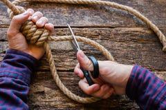 De mens sneed de kabel met een schuifknoop stock afbeeldingen