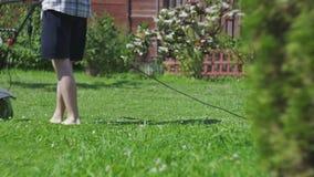 De mens snijdt blootvoets grasgrasmaaimachine stock videobeelden