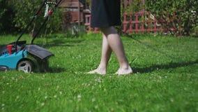 De mens snijdt blootvoets grasgrasmaaimachine stock video