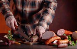 De mens snijdt diverse worsten en gerookt vlees royalty-vrije stock foto's