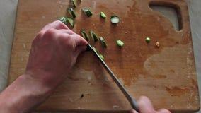 De mens snijdt een komkommer op een houten raad stock video